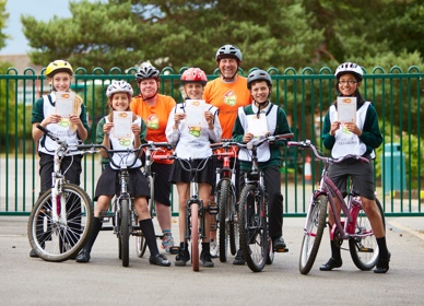 Group of children on their bikes showing off the Bikeability certificates.
